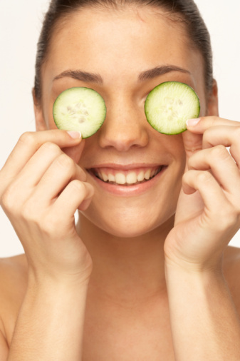 Young woman holding cucumber slice in front of eyes, smiling